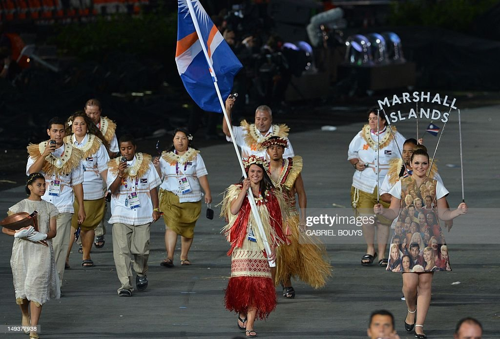 Marshall Islands' flagbearer Haley Nemra (C) leads her delegation during the opening ceremony of the London 2012 Olympic Games on July 27, 2012 at the Olympic Stadium in London. AFP PHOTO / GABRIEL BOUYS