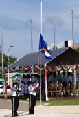 A Marshall Islands police officer raises the national flag to half mast at the March 1 ceremony in Majuro on March 1 to mark the 60th anniversary of...