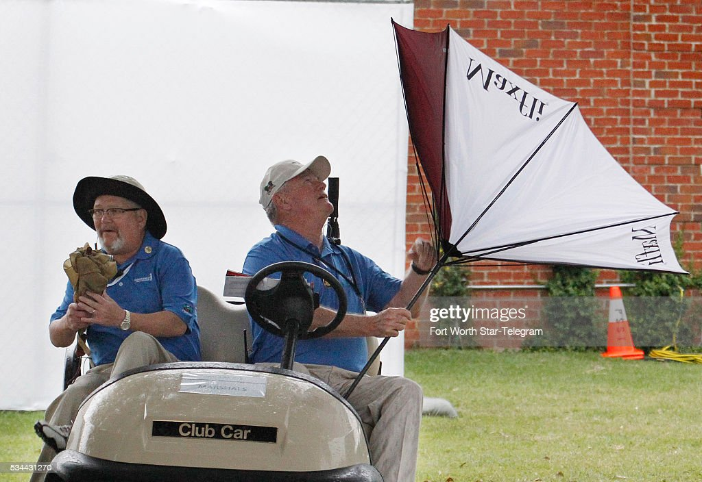 Marshall J.R. Rambo, right, with Drew Martin, left, wrestles with his umbrella turned inside-out during round one of the Dean & DeLuca Invitational Thursday, May 26, 2016, in Fort Worth, Texas. With play suspended at 8:29am, players, fans and marshalls headed for cover.