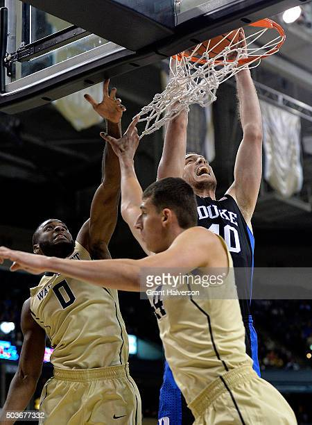 Marshall Plumlee of the Duke Blue Devils dunks over Codi MillerMcIntyre and Konstantinos Mitoglou of the Wake Forest Demon Deacons during their game...