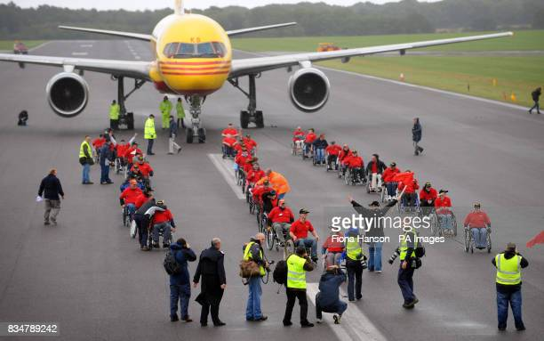 A marshall raises her arms signalling the moment when fifty disabled volunteers prepare to pull a 65 ton Boeing 757 100 meters at Lasham airfield in...