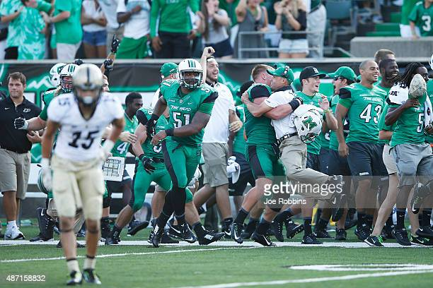Marshall Thundering Herd players and coaches celebrate on the sideline after Tiquan Lang returned an interception for a touchdown late in the second...