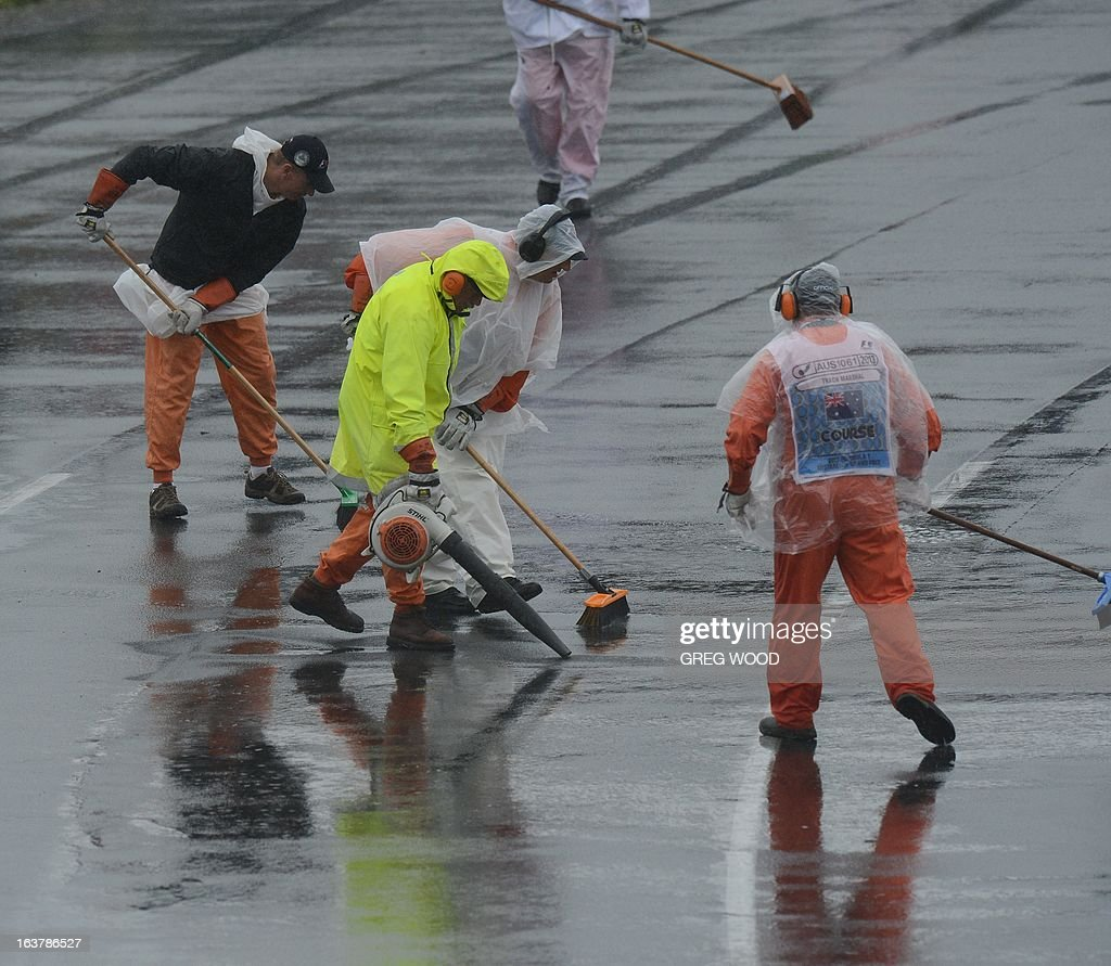 Marshalls attempt to dry the track prior to the qualifying session at the Formula One Australian Grand Prix in Melbourne on March 16, 2013. AFP PHOTO / Greg WOOD USE