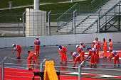 Marshalls clean the track as the session is delayed following a fuel leak on track during practice for the Formula One Grand Prix of Russia at Sochi...