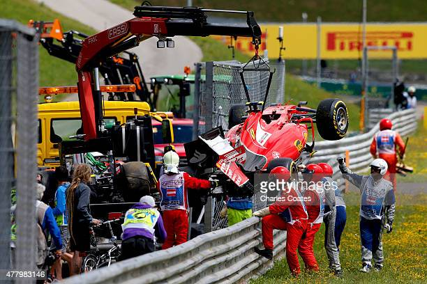 Marshalls retrieve the car of Kimi Raikkonen of Finland and Ferrari after he crashed during the Formula One Grand Prix of Austria at Red Bull Ring on...
