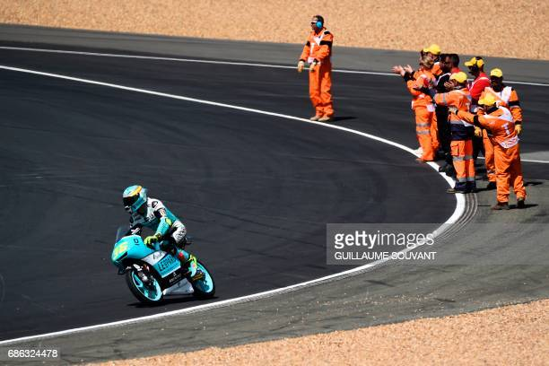 Marshals applaud as winner Spanish's rider Joan Mir on his Leopard racing N°36 drives by at the end of the Moto 3 race of the French motorcycling...