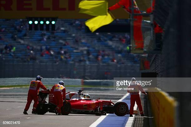 Marshals push Sebastian Vettel of Germany driving the Scuderia Ferrari SF16H Ferrari 059/5 turbo to safety after he stopped on the start finish...