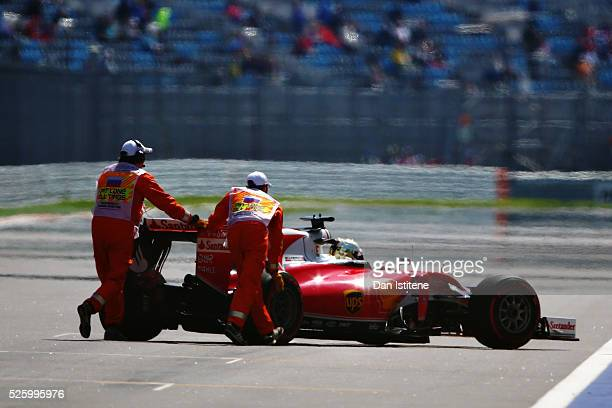 Marshals rescue Sebastian Vettel of Germany driving the Scuderia Ferrari SF16H Ferrari 059/5 turbo after he stopped on the start finish straight...