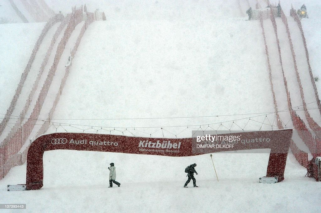 Marshals walk in the finish area of the Streif course in Kitzbuehel on January 20 2012 as the men's World Cup superG event scheduled today has been...