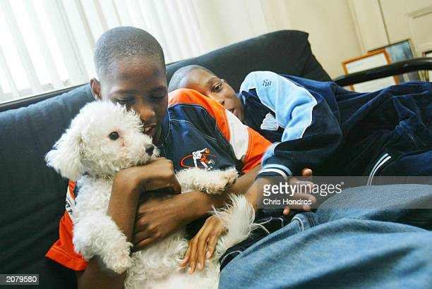 Marshawn and Maleek foster children of Stephen McCall hug a new puppy June 10 2003 in the Crown Heights neighborhood of Brooklyn in New York City...