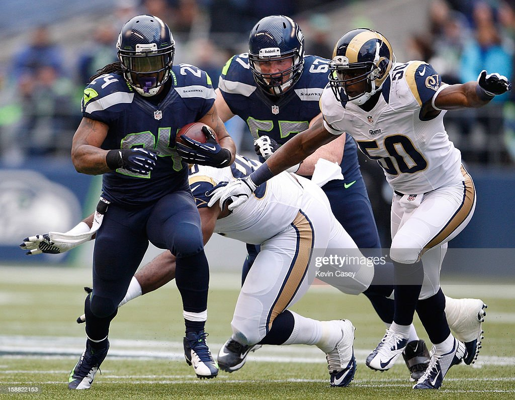 Marshawn Lynch (L) #24 of the Seattle Seahawks runs the ball against the St. Louis Rams at CenturyLink Field on December 30, 2012 in Seattle, Washington.