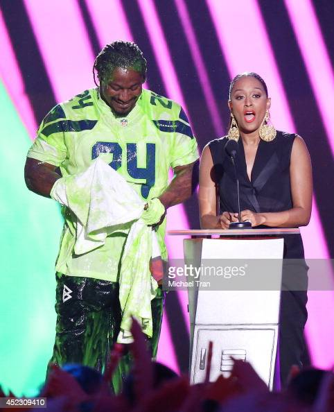 Marshawn Lynch and Tia MowryHardrict speak onstage during the Nickelodeon Kids' Choice Sports Awards 2014 held at Pauley Pavilion on July 17 2014 in...