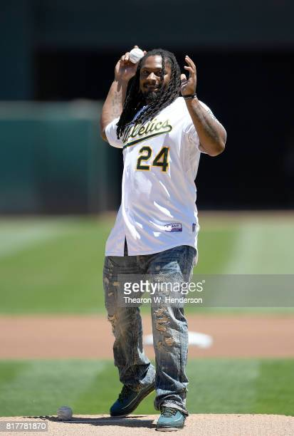 Marshawn Lynch of the Oakland Raiders in beast mode throws out the ceremonial first pitch prior to the start of the game between the Cleveland...