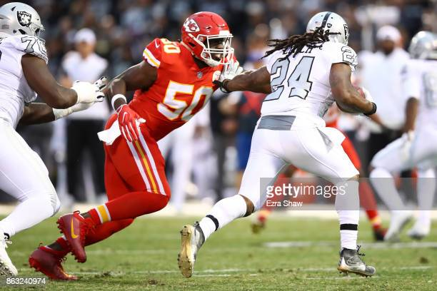 Marshawn Lynch of the Oakland Raiders is pursued by Justin Houston of the Kansas City Chiefs during their NFL game at OaklandAlameda County Coliseum...