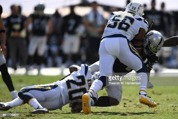 Marshawn Lynch of the Oakland Raiders is tackled by Desmond King and Korey Toomer of the Los Angeles Chargers during their NFL game at OaklandAlameda...