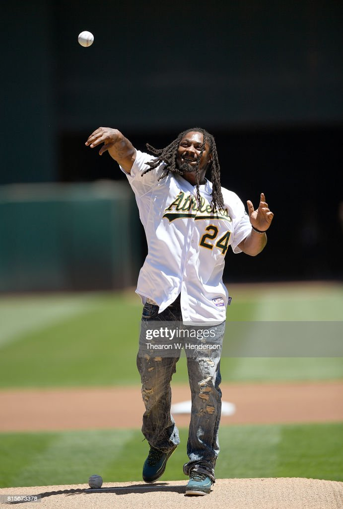 Marshawn Lynch #24 of the Oakland Raiders throws out the ceremonial first pitch prior to the start of the game between the Cleveland Indians and Oakland Athletics at Oakland Alameda Coliseum on July 16, 2017 in Oakland, California.