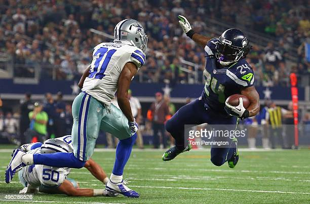 Marshawn Lynch of the Seattle Seahawks carries the ball against Sean Lee of the Dallas Cowboys and Byron Jones of the Dallas Cowboys in the second...