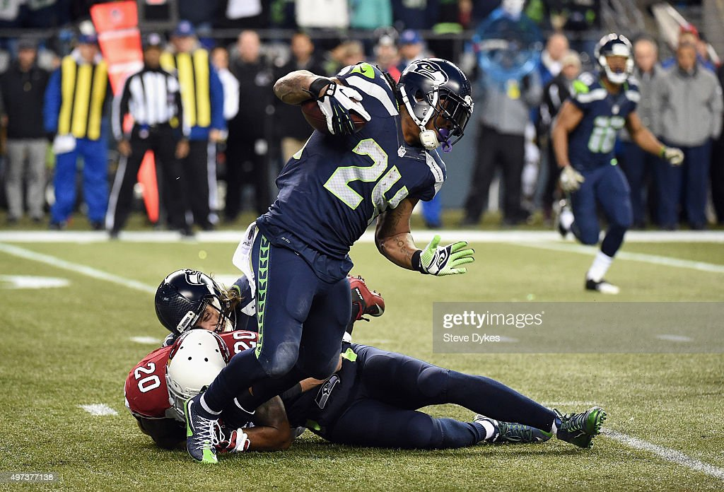 Marshawn Lynch #24 of the Seattle Seahawks is tackled by Deone Bucannon #20 of the Arizona Cardinals as he carries the ball during the first half at CenturyLink Field on November 15, 2015 in Seattle, Washington.