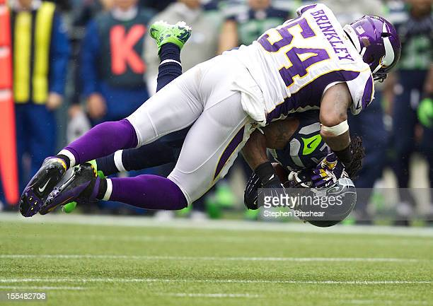 Marshawn Lynch of the Seattle Seahawks is tackled by Jasper Brinkley of the Minnesota Vikings during game at CenturyLink Field on November 4 2012 in...