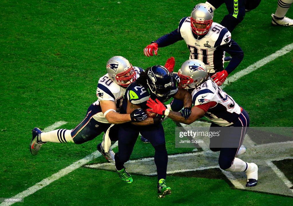 Marshawn Lynch #24 of the Seattle Seahawks is tackled by Rob Ninkovich #50 and Dont'a Hightower #54 of the New England Patriots during Super Bowl XLIX at University of Phoenix Stadium on February 1, 2015 in Glendale, Arizona.