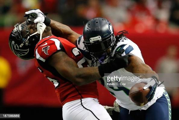 Marshawn Lynch of the Seattle Seahawks stiff arms William Moore of the Atlanta Falcons at Georgia Dome on November 10 2013 in Atlanta Georgia