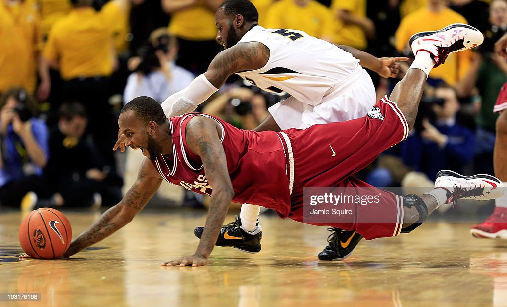 Marshawn Powell #33 of the Arkansas Razorbacks and Keion Bell #5 of the Missouri Tigers dive for a loose ball during the game at Mizzou Arena on March 5, 2013 in Columbia, Missouri.