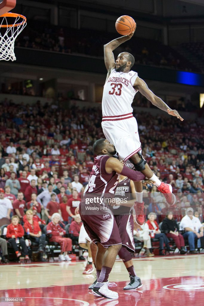 Marshawn Powell #33 of the Arkansas Razorbacks goes up for a dunk over Trivante Bloodman #4 of the Mississippi State Bulldogs but is called for a charge at Bud Walton Arena on January 23, 2013 in Fayetteville, Arkansas. The Razorbacks defeated the Bulldogs 96-70.