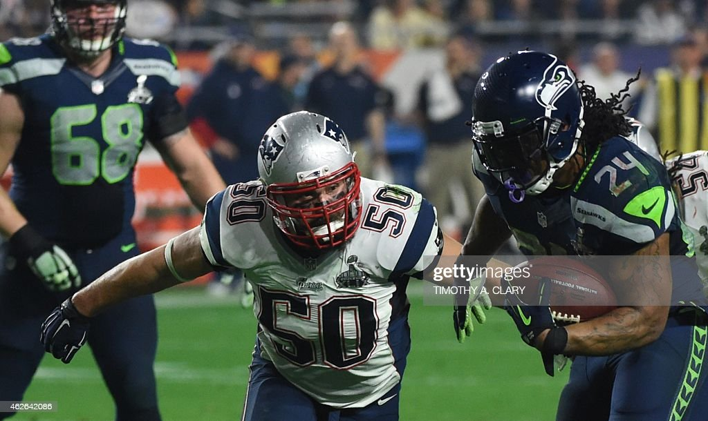 Marshawn Wagner of the Seattle Seahawks moves the ball against Rob Ninkovitch of the New England Patriots during Super Bowl XLIX February 1 2015 at...