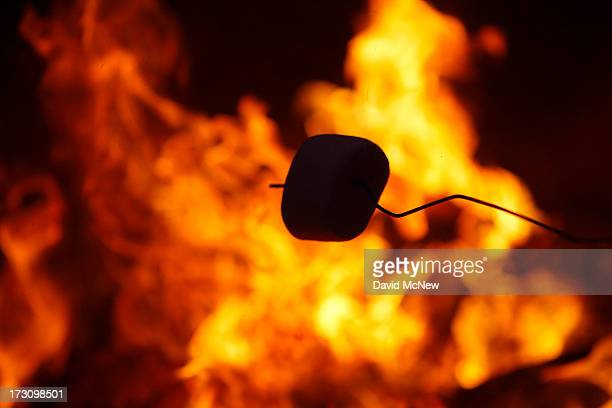 A marshmallow is roasted as beach goers gather around traditional beach bonfires on July 6 2013 in Huntington Beach California Beach fires are a long...