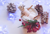 Funny marshmallow snowman in red cup of hot chocolate