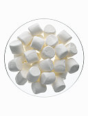 Marshmallows in glass bowl on white background