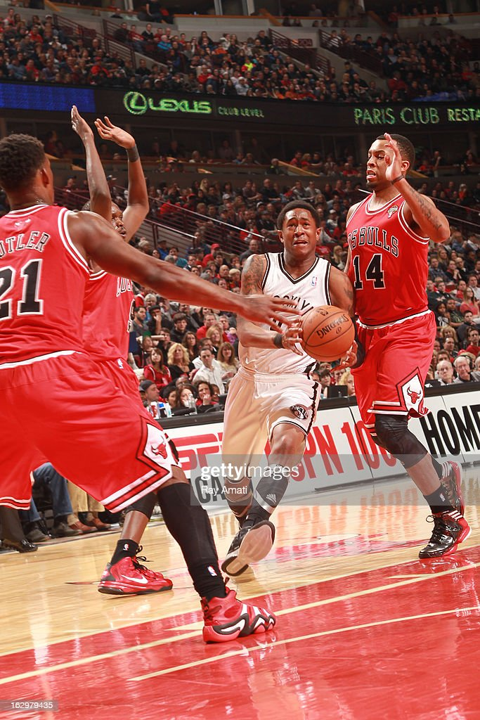 MarShon Brooks #9 of the Brooklyn Nets drives between Jimmy Butler #21 and Daequan Cook #14 of the Chicago Bulls on March 2, 2013 at the United Center in Chicago, Illinois.