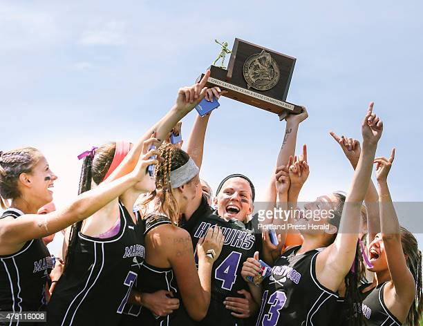 Marshwood High School girls lacrosse team hoist the Girls Class A lacrosse championship trophy above their heads after a victory against Messalonskee...