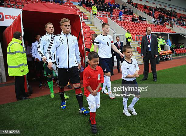 Mart Ristl of the Germany and Bryn Morris of the England lead their teams out ahead of the Under 18 International Friendly match between England U18...