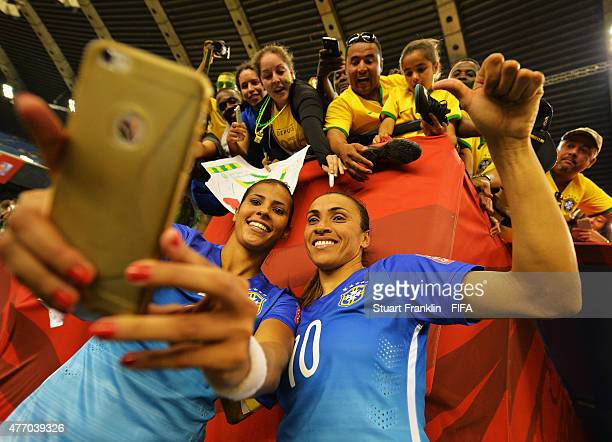 Marta and Fabiana of Brazil make a selfie with fans after the FIFA Women's World Cup 2015 group E match between Brazil and Spain at Olympic Stadium...