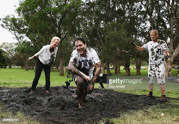 Marta DusseldorpMichael Wipfli Terri Biviano and Greig Pickhaver participate in a mud fight to raise awareness about the 'Mud Pie Project' to help...