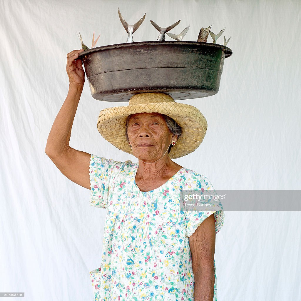 Marta Layaog fish saleswoman carrying fish for sale on her head Pooc Bantayan Island The Philippines Every morning at 7 am fisherwomen meet fishermen...