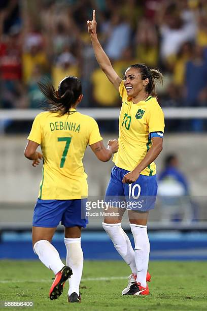 Marta of Brazil celebrates with teammate Debora after scoring Brazil's fourth goal during the Women's Group E first round match between Brazil and...