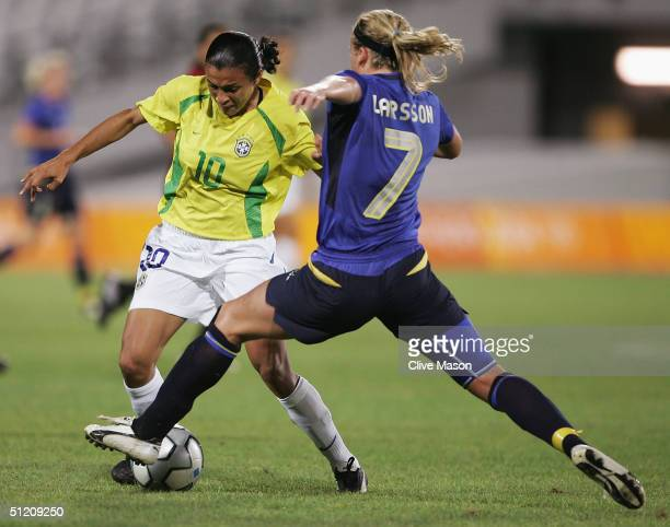 Marta of Brazil pushes past Sara Larsson of Sweden during the women's football semifinal match on August 23 2004 during the Athens 2004 Summer...