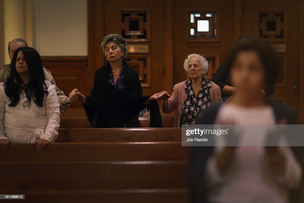 Marta Soto (C) and Maria Elena de la Vega (2nd R) and others pray during a service at the Church of the Little Flower on February 11, 2013 in Coral Gables, Florida. Parishioners today were dealing with the unexpected news that Pope Benedict XVI announced his retirement, now the wait begins to learn who his successor will be.
