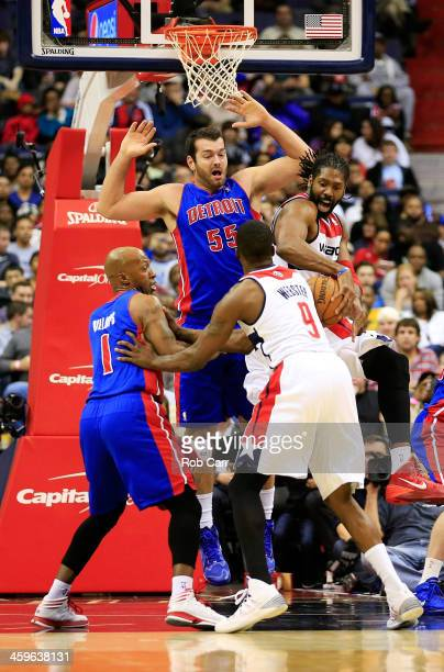 Martell Webster looks on as Nene Hilario of the Washington Wizards pulls down a rebound in front of Josh Harrellson and Chauncey Billups of the...
