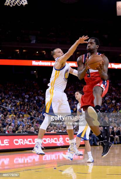 Martell Webster of the Washington Wizards attemps a layup over Stephen Curry of the Golden State Warriors at ORACLE Arena on January 28 2014 in...