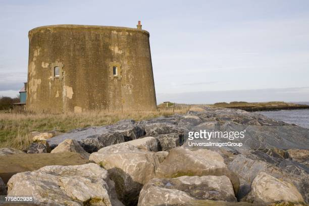 Martello tower defended from erosion by rock armor at East Lane Bawdsey Suffolk England