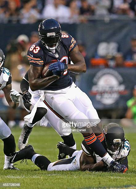 Martellus Bennett of the Chicago Bears is tackled by Johnathan Cyprien of the Jacksonville Jaguars during a preseason game at Soldier Field on August...