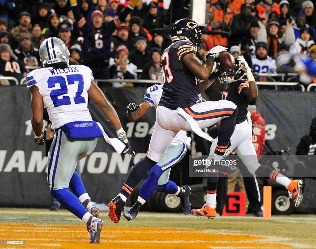 Martellus Bennett #83 of the Chicago Bears makes a touchdown catch between J.J. Wilcox #27 of the Dallas Cowboys and Brandon Carr #39 of the Dallas Cowboys during the second quarter of a game at Soldier Field on December 4, 2014 in Chicago, Illinois.