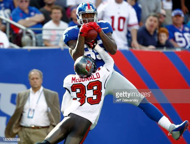 Martellus Bennett of the New York Giants pulls in a pass for a touchdown with coverage by Brandon McDonald of the Tampa Bay Buccaneers during a game...