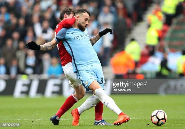 Marten de Roon of Middlesbrough puts pressure on Nicolas Otamendi of Manchester City during The Emirates FA Cup QuarterFinal match between...