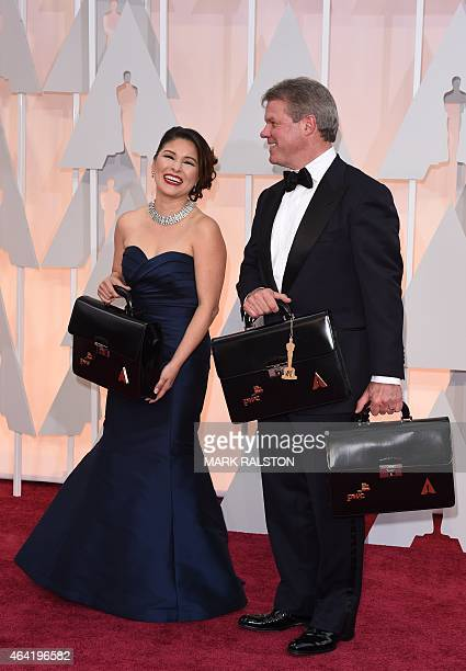 Martha L Ruiz and Brian Cullinan carry the envelops of the winners on the red carpet for the 87th Oscars on February 22 2015 in Hollywood California...