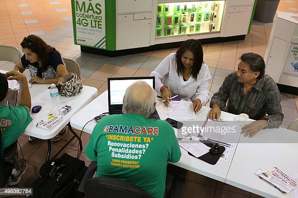 Martha Lucia Bienvendida Barreno and Jorge Baquero sit with insurance agents from Sunshine Life and Health Advisors as they discuss plans available...