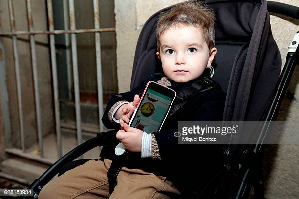 Marti Fabregas is wearing a HM wool cap HM trousers a Zara kids jacket Adidas trainers an iPhone 6S and a Bugaboo baby carriage at the Palo Market on...